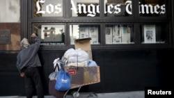 """Seorang pria tunawisma membaca berita di jendela kantor harian """"Los Angeles Times"""" di Los Angeles, California (foto: ilustrasi)."""