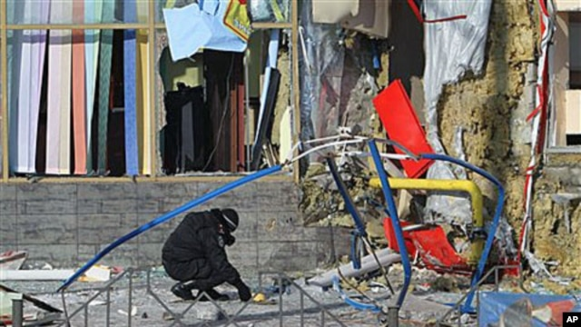 An investigator works at the scene of one of two explosions near the city's market in the eastern Ukrainian town of Makiyivka, 20 Jan 2011