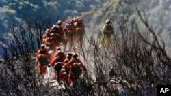 In this photo provided by the Santa Barbara County Fire Department, CAL FIRE Inmate Firefighting Hand Crew members hike through the charred landscape on their way to work east of Gibraltar Road above Montecito, Calif., Tuesday, Dec. 19, 2017.