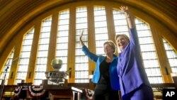 Democratic presidential candidate Hillary Clinton, accompanied by Sen. Elizabeth Warren, D-Mass., left, waves after speaking at the Cincinnati Museum Center at Union Terminal in Cincinnati, June 27, 2016.