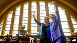 Democratic presidential candidate Hillary Clinton, accompanied by Sen. Elizabeth Warren, D-Mass., left, waves after speaking at the Cincinnati Museum Center at Union Terminal in Cincinnati, June 27, 2016.