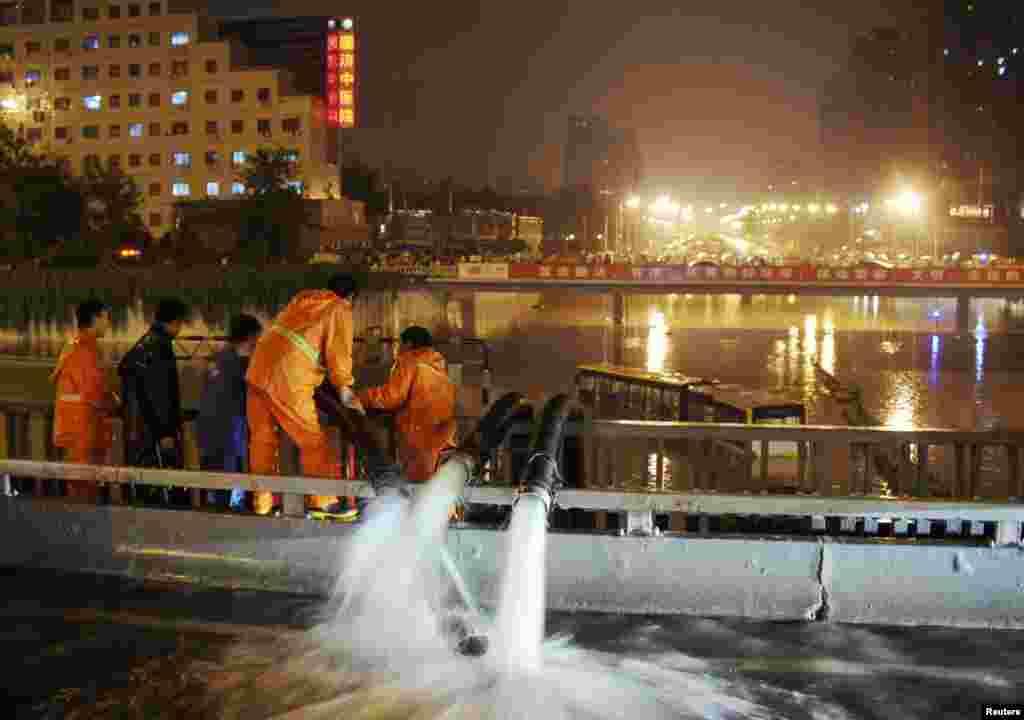 Công nhân bơm nước lụt gần một chiếc xe lớn bị mắc kẹt do mưa lũ tại Bắc Kinh, 21/7/2012.