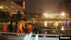 工作人员用水泵为北京街道排水,附近是一辆因大水被遗弃街头的巴士(7月21日)