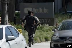 3일 캘리포니아 샌브루노에 있는 유튜브 본사 건물 밖에서 권총을 난사 사건이 발생한 후 경찰관이 사건 현장을 향해 뛰어가고 있다.