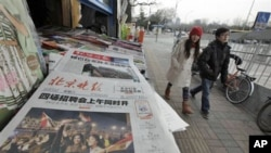 A Chinese couple walks past a newspaper front page showing Egyptians celebrating and title 'Mubarak hands over power' at a newsstand in Beijing, China, February 12, 2011