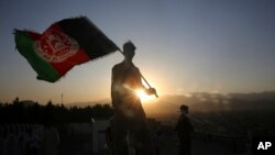 A man waves an Afghan flag during Independence Day celebrations in Kabul, Afghanistan, Monday, Aug. 19, 2019. (AP Photo/Rafiq Maqbool)