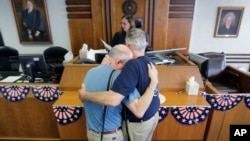 FILE - After the U.S. Supreme Court ruled that same-sex couples have the right to marry nationwide, Gerald Gafford, right, and his partner of 28 years, Jeff Sralla, receive a waiver allowing them to marry, in Austin, Texas, June 26, 2015.