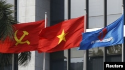 FILE PHOTO: Flag of PetroVietnam flutters next to Vietnamese national flag and Communist Party flag in front of the headquarters of PetroVietnam in Hanoi Jan. 11, 2016.