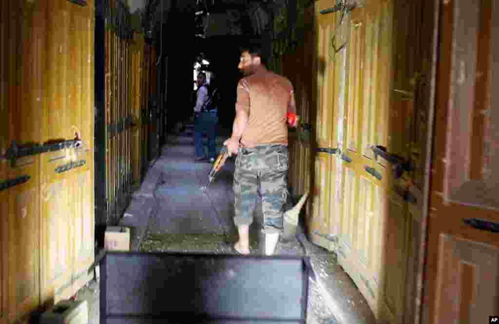 Một thành viên của Quân đội Giải phóng Syria tuần tra qua một con hẻm của thành phố Aleppo, ngày 16/10/2012.