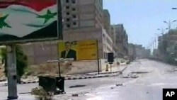 """Image released by the Syrian official news agency SANA, empty streets with debris are shown of what SANA describes as the Syrian army restoring """"security and stability"""" to the central city of Hama, August 4, 2011"""