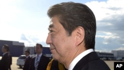 Japanese Prime Minister Shinzo Abe, foreground and his wife, Akie, arrive at the Helsinki International Airport in Vantaa, Finland, July 9, 2017.