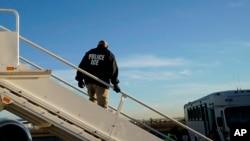 Seorang petugas mengawasi saat para imigran yang masuk ke wilayah AS secara ilegal dideportasi dengan penerbangan ke El Salvador oleh Kantor Imigrasi dan Penegakan Bea Cukai di Houston, 16 November 2018.