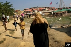A Rohingya Muslim woman covers her face from the afternoon dust and heat as she walks through Jamtoli refugee camp, Nov. 27, 2017, in Bangladesh. Since late August, more than 630,000 Rohingya have fled Myanmar's Rakhine state into neighboring Bangladesh.