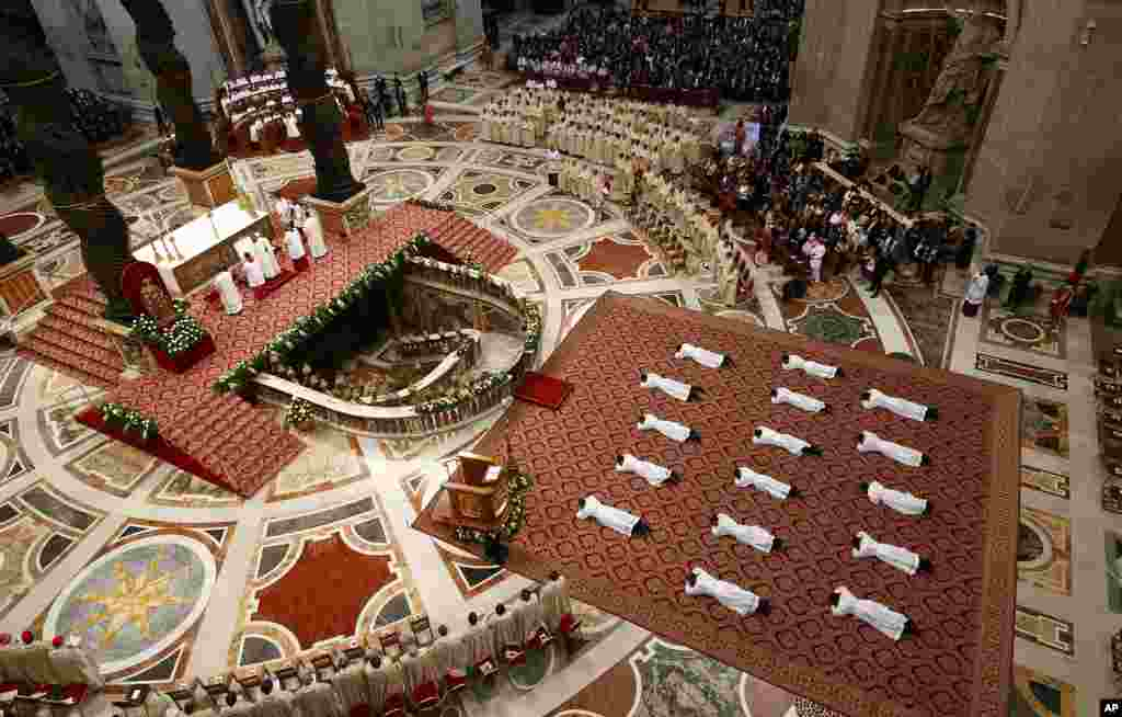 New priests lie face down on the floor during an ordination ceremony presided over by Pope Francis, in St. Peter's Basilica at the Vatican.