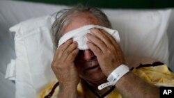 Seorang pasien flu meletakkan kompres dingin di kepalanya, di Pusat Kesehatan Wilayah Upson, Thomaston, Ga., 9 Februari 2018.