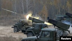 FILE - Ukrainian servicemen fire BM-21 Grad multiple rocket launcher systems during military exercises near the village of Divychky in the Kyiv region of Ukraine, Oct. 28, 2016.