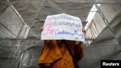 """Phra Shine Waradhammo, biksu Thailand, memegang pakat bertuliskan """"Hentikan Mengutuk Aborsi"""" dalam aksi demo di depan parlemen Thailand di Bangkok, 25 Januari 2021. (Foto: Krit Phromsakla Na Sakolnakorn / Thai News Pix)."""