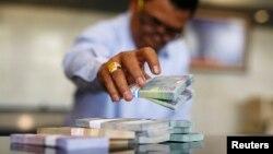 Pegawai Bank Indonesia menghitung rupiah di kantor pusat di Jakarta.