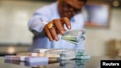 Seorang pegawai Bank Indonesia menghitung lembaran uang rupiah di kantor pusat di Jakarta.