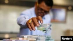 Seorang kasir di Bank Indonesia menghitung lembaran-lembaran kertas rupiah.