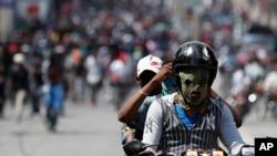 Yon manifestan kji sou yon moto ak yon mask nan figi l. Foto Achiv: Pòtoprends, Ayiti
