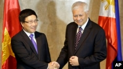 Philippine Foreign Affairs Secretary Albert Del Rosario, right, welcomes Vietnamese Foreign Minister Pham Binh Minh for their 7th Meeting of the Philippines-Vietnam Joint Commission for Bilateral Cooperation (JCBC) in Manila, Philippines, Aug. 1, 2013 .