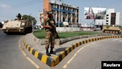 An army soldier stands guard on a road leading to a polling station during a re-polling for the general elections in Karachi, May 19, 2013.