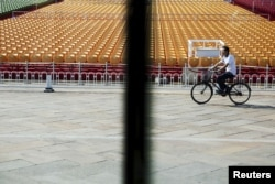 A man cycles past stands raised at Beijing's Tiananmen Square, Sept. 2, 2015, as the capital prepares for massive military parade.