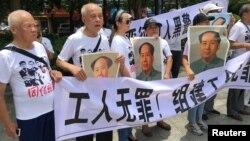 人们在中国广东省深圳市坪山区燕子岭派出所外示威,手持标语,支持佳士工厂工人组建工会要求。(2018年8月6日)