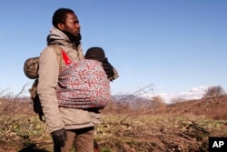 FILE - Jean-Paul Apetey of Ivory Coast helps carrying a baby near the village of Udovo, Macedonia, March 3, 2015.