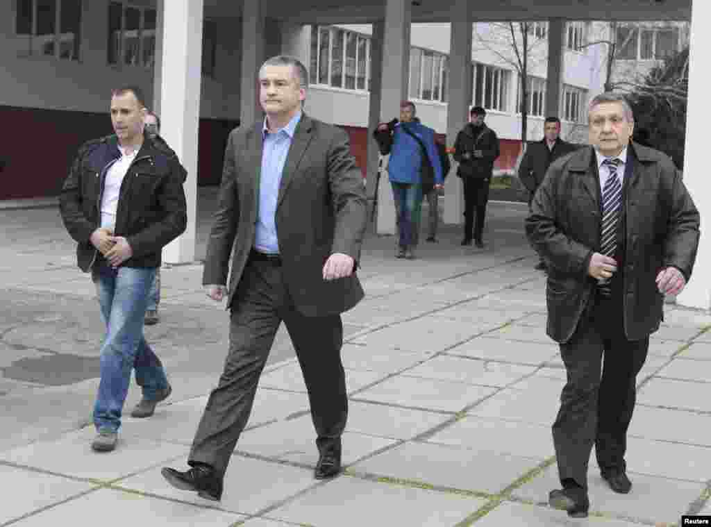 Crimean Prime Minister Sergei Aksyonov (C) leaves after casting his ballot during voting in a referendum at a polling station in Simferopol, Crimea, Ukraine, March 16, 2014.