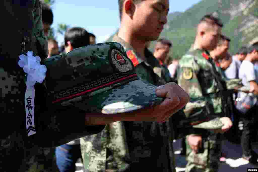 អ្នកជួយសង្គ្រោះ និងអ្នកស្រុកស្មឹងស្មាត នៅពេលពួកគេចូលរួមក្នុងកម្មវិធីកាន់ទុក្ខជាសាធារណៈសម្រាប់ជនរងគ្រោះនៃការបាក់ដីនៅក្នុងភូមិ Xinmo ខេត្ត Sichuan ប្រទេសចិន។