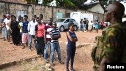 Un militaire assure la sécurité près des électeurs en fils lors du deuxième tour de la présidentielle à Freetown, Sierra Leone, 31 mars 2018.