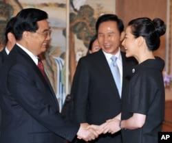 2008年8月25日中国主席胡锦涛和韩国演员李英爱在首尔参加宴会前握手,韩国总统李明博在旁观看