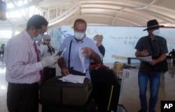 Petugas memeriksa penumpang dari Australia di bandara Ngurah Rai, di Denpasar, Bali (foto: ilustrasi).