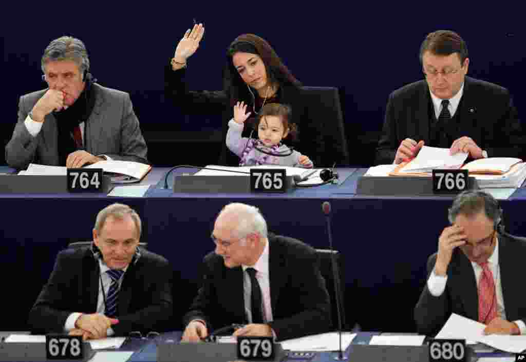 Italy's Member of the European Parliament Licia Ronzulli takes part with her daughter in a voting session at the European Parliament in Strasbourg February 15, 2012. (Reuters)