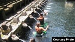 Turis asing mandi-mandi di air mancur Tirta Empul di Bali.