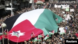 Protesters from Jordanian opposition parties carry a giant national flag while shouting anti-government slogans during a demonstration against what they say are worsening economic conditions, after Friday prayers in Amman February 25, 2011. The protests i