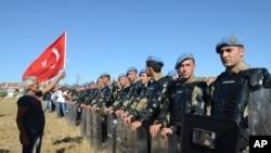 Seorang demonstran berdiri di depan barikade polisi paramiliter yang menjaga agar ribuan orang tidak masuk ke kompleks penjara Silivri, Turki (5/8).