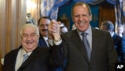 El ministro de Exteriores ruso, Sergey Lavrov (derecha) y su contraparte siria, Walid al-Maolem entran a un salón de la mano, para conversar en Moscú.