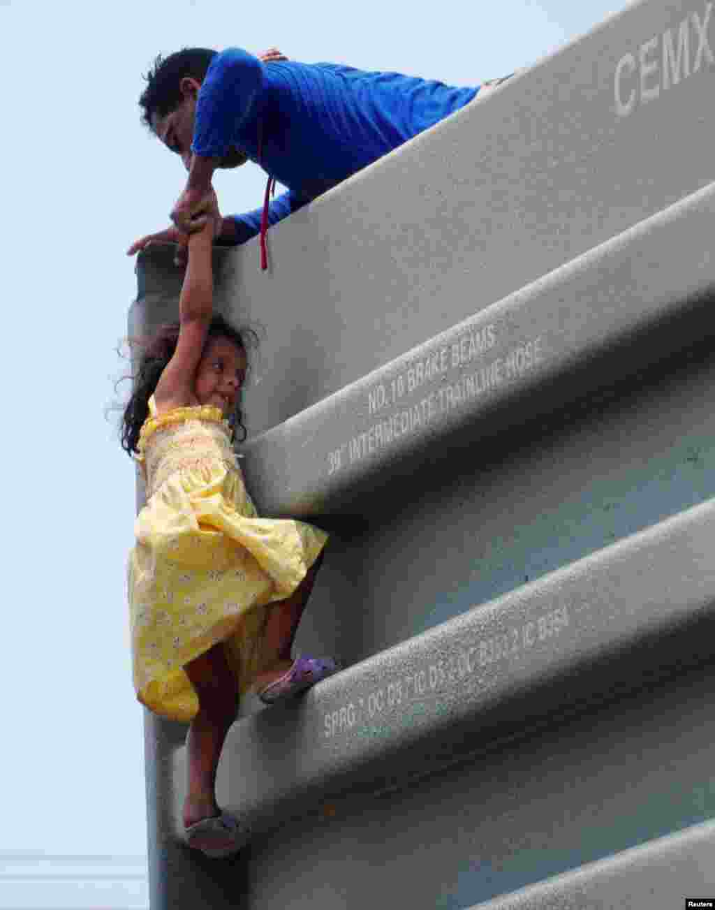 "A man helps a girl to climb onto a boxcar as they join other Central American migrants (not pictured) in the freight train known as ""The Beast"" in Ixtepec, Mexico, during their journey toward the United States, April 30, 2019."