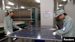 FILE - Employees work on a solar panel production line at Suntech Power Holdings headquarters in Wuxi, Jiangsu. The past few years has seen a plethora of trade disputes as China-made environmental equipment, including solar panels, flooded into western markets.