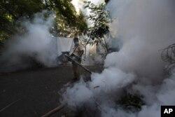 Seorang pegawai Mumbai Municipal Corp. menyemprot jalan di Mumbai, India, 10 Juni 2020, untuk mencegah wabah demam berdarah. (Foto: Reuters)