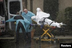 Medics transport a patient through heavy rain into an ambulance at Life Care Center of Kirkland, the long-term care facility linked to several confirmed coronavirus cases in the state, in Kirkland, Washington, March 7, 2020.
