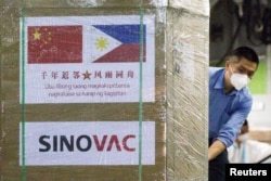 FILE - A worker unloads a box of Sinovac Biotech's CoronaVac vaccines from a Chinese military aircraft at Villamor Air Base in Pasay, Metro Manila, Philippines, Feb. 28, 2021.