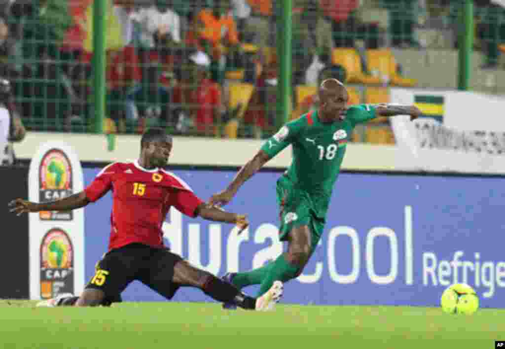 """Qulami Miguel Geraldo (L) of Angola fights for the ball with Kabore Charles of Burkina Faso during the African Nations Cup soccer tournament in Estadio de Malabo """"Malabo Stadium"""", in Malabo January 22, 2012."""