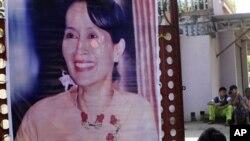 ສະມາຊິກຂອງພັກ National Democratic Force party (NDF) ຜູ້ນຶ່ງ ເອົາຮູບ ຂອງທ່ານນາງ ອອງຊານ ຊູຈີ ຜູ້ນໍາປະຊາທິປະໄຕໃນມຽນມາ ທີ່ຖືກກັກໂຕໃຫ້ຢູ່ແຕ່ໃນບໍລິເວນບ້ານເຮືອນນັ້ນ ຕິດໃສ່ປະຕູເຂົ້າ ສຳນັກງານໃຫຍ່ຂອງພັກ ໃນນະຄອນຢ້າງກຸ້ງ ໃນວັນສຸກ ທີ 5 ພະຈິກ, 2010. (AP Photo/Khin Maun