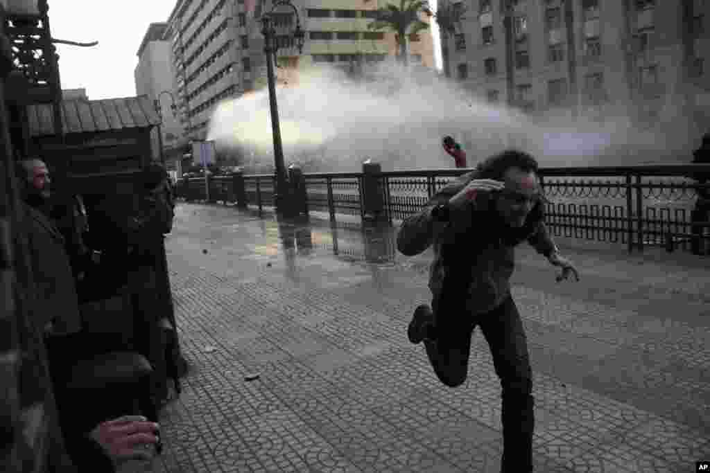 A man runs from a police water cannon in Cairo, Jan. 25, 2011.