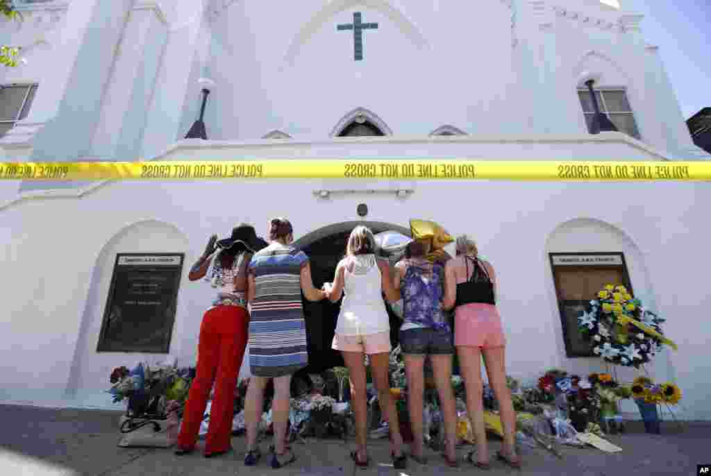 A group of women pray together at a makeshift memorial on the sidewalk in front of the Emanuel AME Church, June 18, 2015 in Charleston, South Carolina.