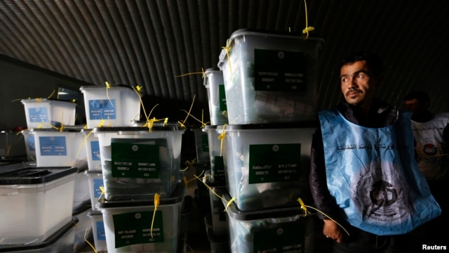 An Afghan election worker stands next to ballot boxes at a counting centre in Kabul, April 6, 2014.